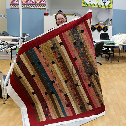 Kim shows off her jelly roll quilt after using a longarm quilting machine at Quilted Joy