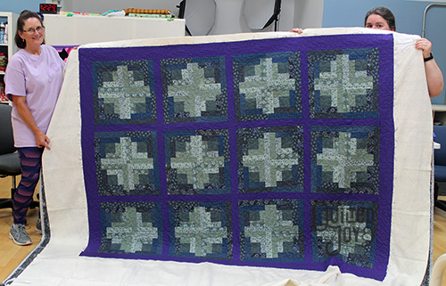 Kim shows off her log cabin quilt after quilting it on a longarm machine at Quilted Joy