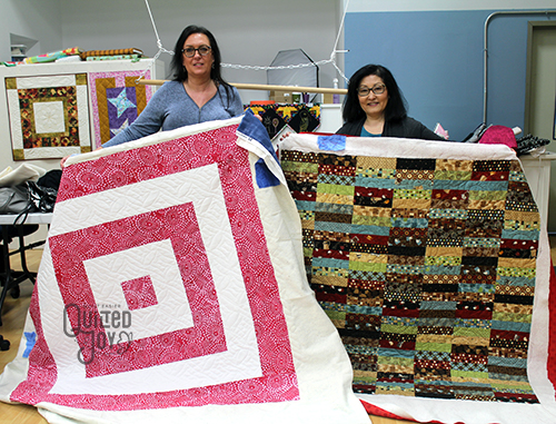 Robin and Grace show off their quilts from the longarm rental certification class at Quilted Joy