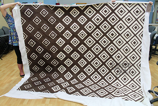 Carol shows off her brown and cream quilt after renting a longarm machine at Quilted Joy