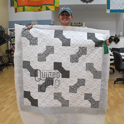 Jennifer poses with the bow tie block quilt she quilted at Quilted Joy