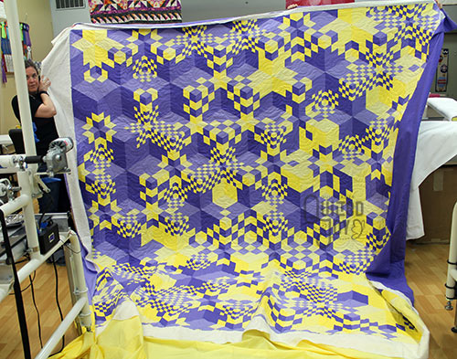 Marie shows off her optical illusion quilt after quilting it on a longarm machine at Quilted Joy