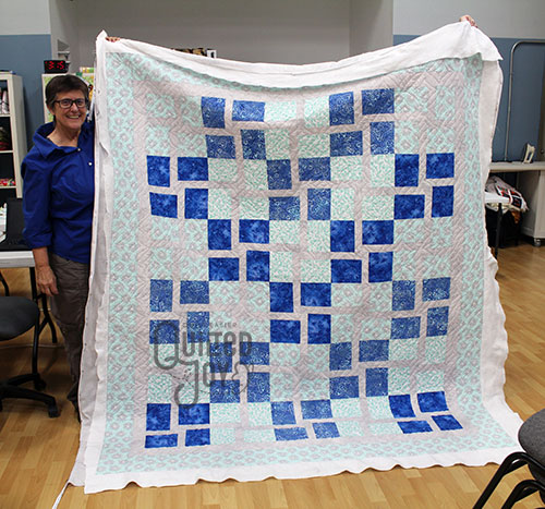 Pam shows off her 2 color quilt after longarm quilting it at Quilted Joy