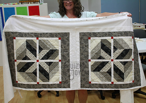 Laura's grey pillow shams after quilting on a longarm quilting machine at Quilted Joy