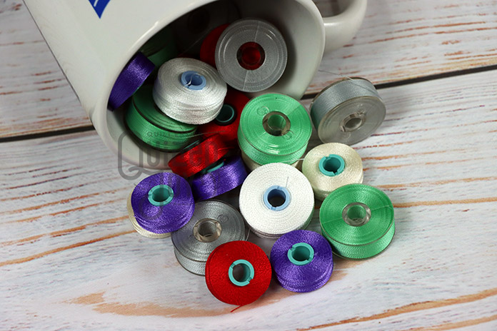 Prewound bobbins spill out of a cup