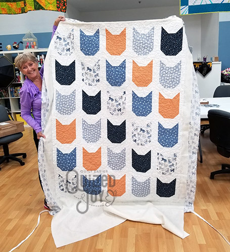 Cheri's cat quilt after longarm quilting it at Quilted Joy