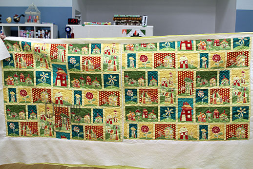 Peggy's whimsical houses quilt after longarm quilting it at Quilted Joy