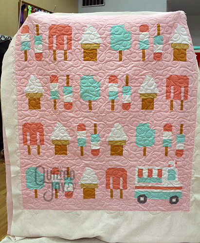 Colleen shows off her Sweet Treat Quilt after longarm quilting it at Quilted Joy