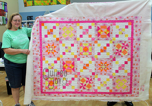 Kathy shows off her pink sampler quilt after longarm quilting it at Quilted Joy