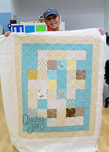 Lisa shows off her cowboy quilt after longarm quilting it at Quilted Joy
