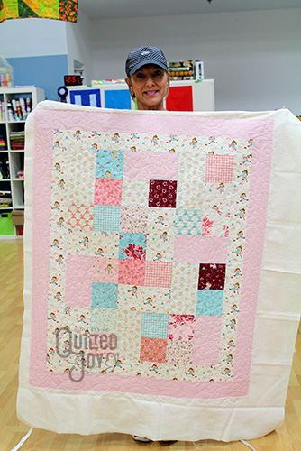 Lisa shows off her Cowgirl quilt after longarm quilting it at Quilted Joy