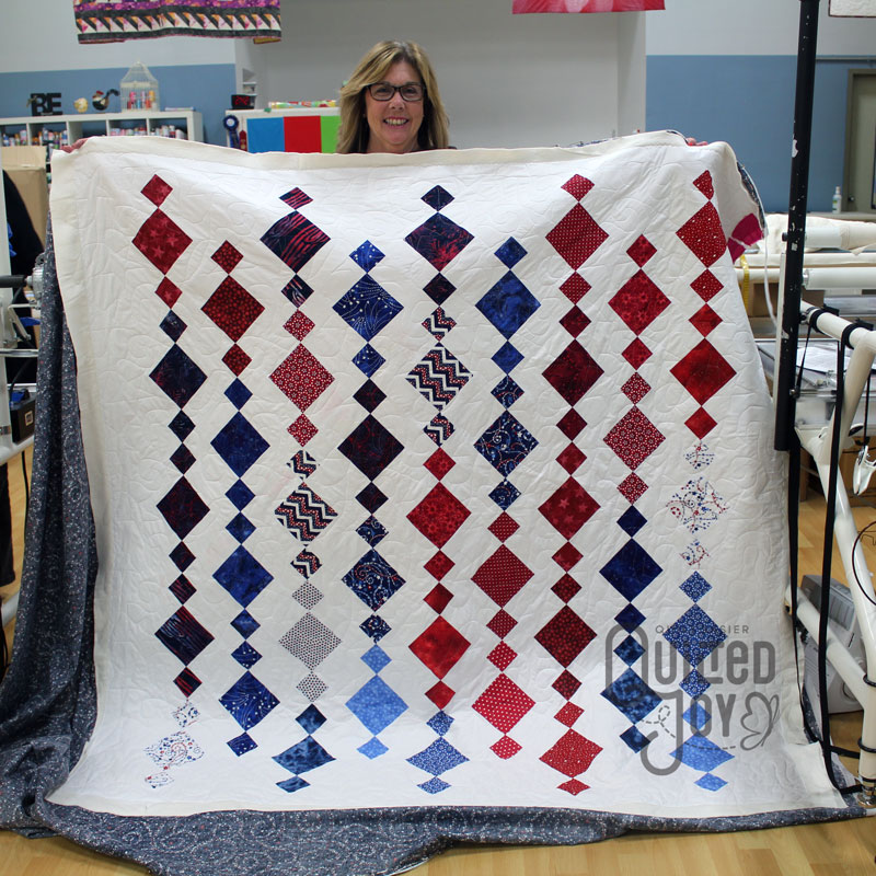 Cheri shows off her quilt after renting a longarm machine at Quilted Joy