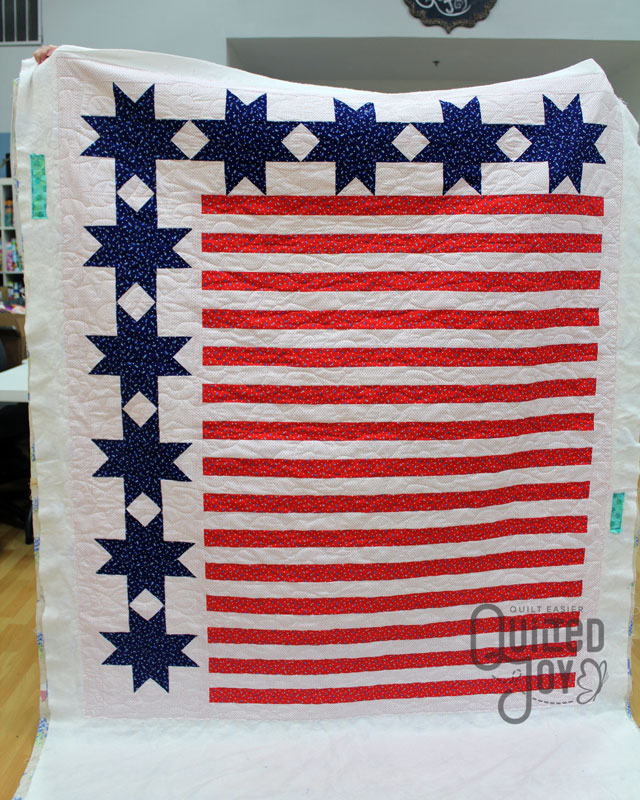 Karen shows off her Stars and Stripes Quilt after renting a longarm machine at Quilted Joy