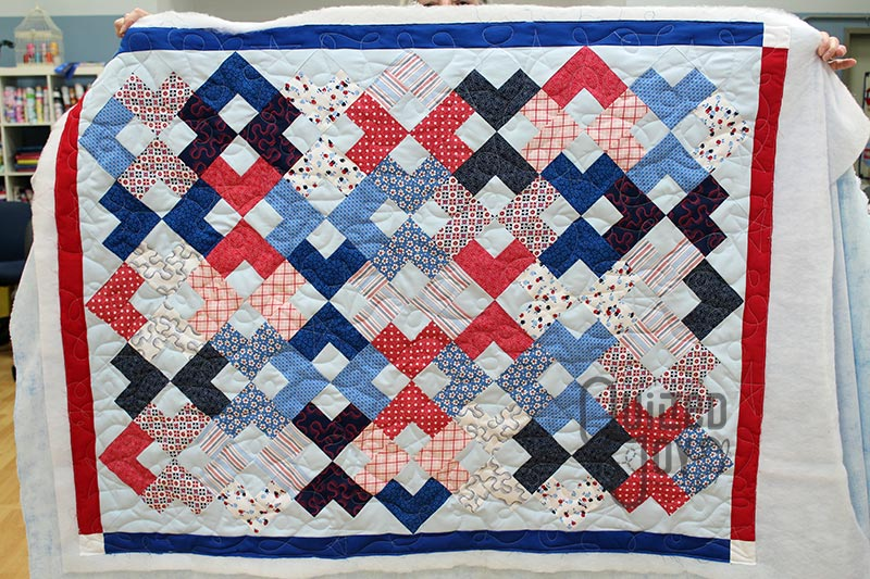Valerie shows off her Chainlink Quilt after longarm quilting it at Quilted Joy