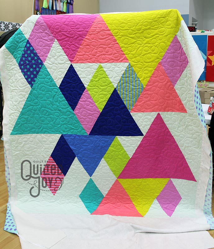 Colleen shows off her modern mountain quilt after her longarm rental at Quilted Joy