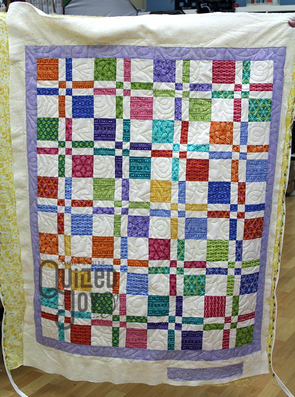 Judy shows off her disappearing four patch quilt after renting a longarm machine at Quilted Joy