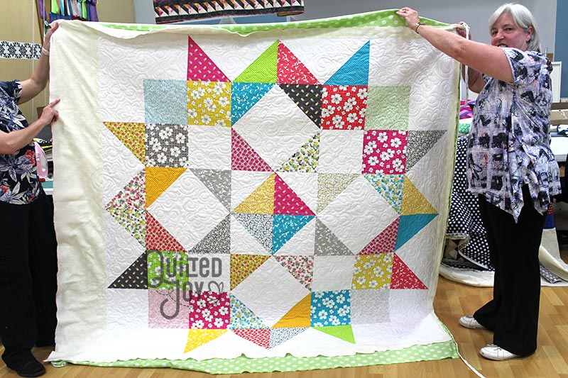 Valerie shows off her XL star quilt after renting a longarm machine at Quilted Joy