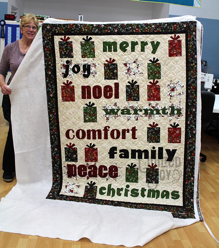 Carol shows off her Christmas quilt after longarm quilting it at Quilted Joy