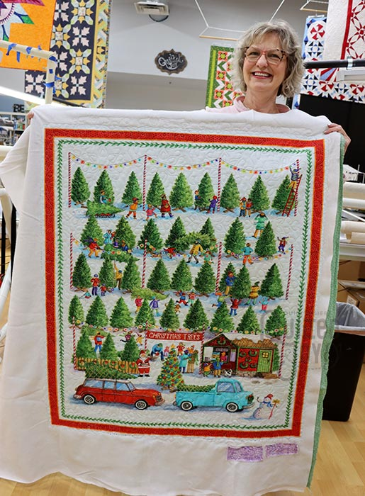 Cathy shows off her Christmas Trees Panel Quilt after quilting it at Quilted Joy