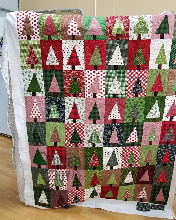 Colleen shows off her Modern Christmas Tree quilt after quilting it at Quilted Joy