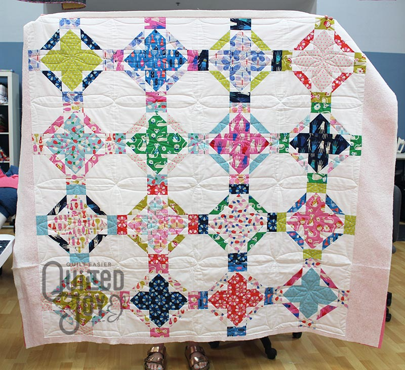 Erin shows off her quilt after renting a longarm at Quilted Joy