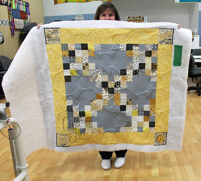 Brenda shows off her Bee Joyful quilt after renting a longarm machine at Quilted Joy