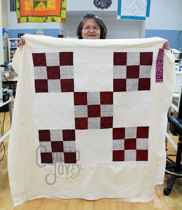 Carol shows off her 9 patch quilt after renting a longarm machine at Quilted Joy