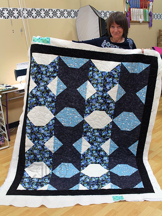 Karen shows off her cat block quilt after renting a longarm machine at Quilted Joy