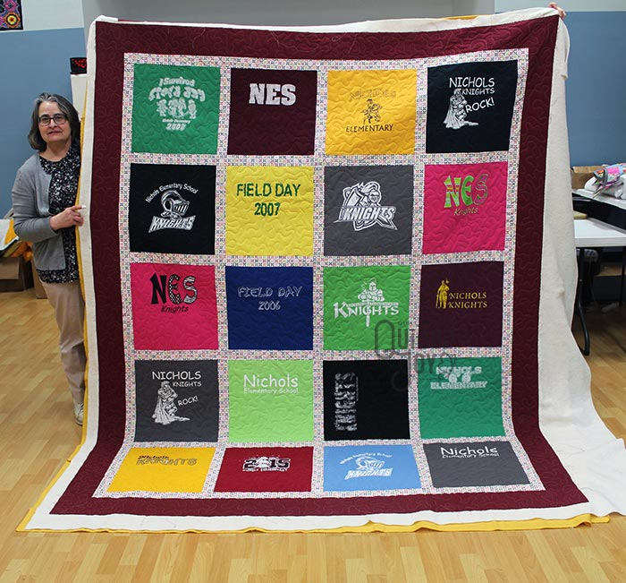 Trina shows off her T-shirt quilt after renting a longarm machine at Quilted Joy