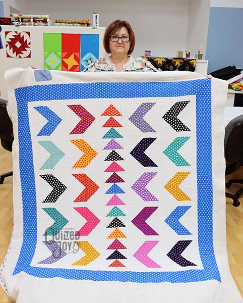 Falicia shows off her Polka Dots and Flying Geese Quilt after renting a longarm machine at Quilted Joy