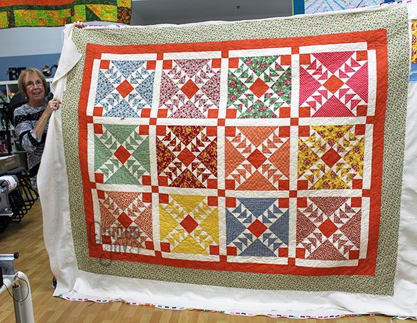 Jennifer shows off her flying geese quilt after renting a longarm machine at Quilted Joy