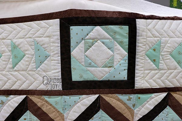 Rebecca shows off her custom quilted quilt after renting a longarm machine at Quilted Joy