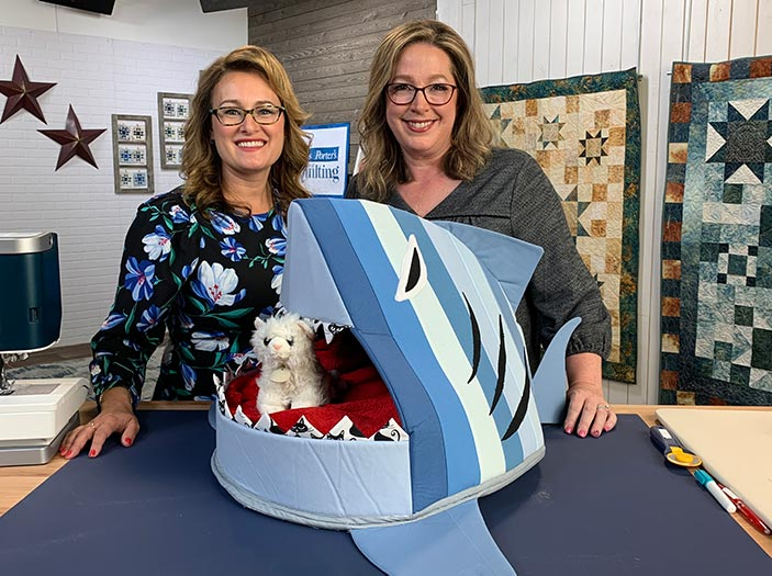 Angela Huffman and Sara Gallegos with the Shark Bait Cat bed on the set of Love of Quilting tv show