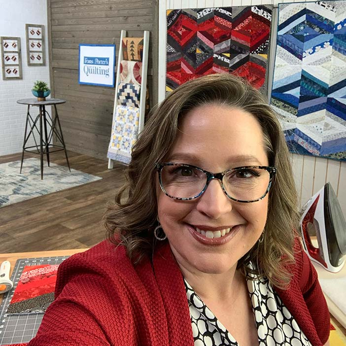 Angela Huffman on the set of Love of Quilting TV with her improv string quilts in the background
