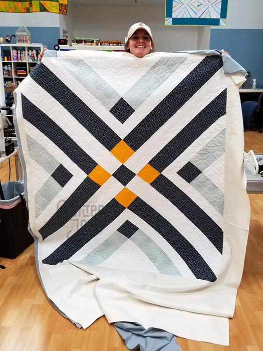 Jennifer shows off her bold diagonals quilt after renting a longarm machine from Quilted Joy
