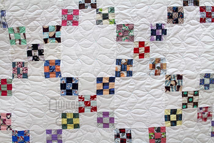 Rena shows off her custom quilted Irish Chain quilt after renting a longarm machine at Quilted Joy
