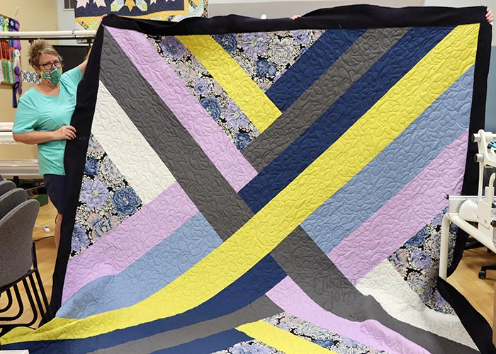 Sandra shows off her quilt with bold diagonals after renting a longarm machine at Quilted Joy
