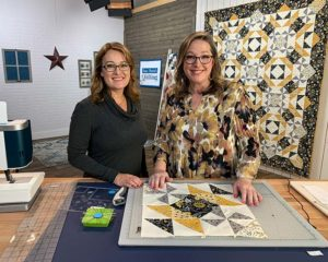 image of Angela Huffman and Sara Gallegos on Love of Quilting film set with a yellow and gold quilt called All the Buzz hanging in the background