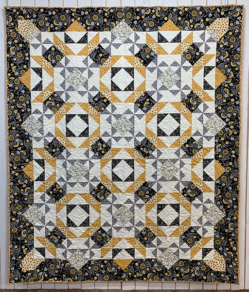 image of All the Buzz Quilt, this quilt is black, white, and gold.