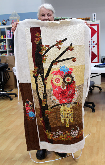 Jane shows off her Cora the Owl quilt after renting a longarm machine at Quilted Joy