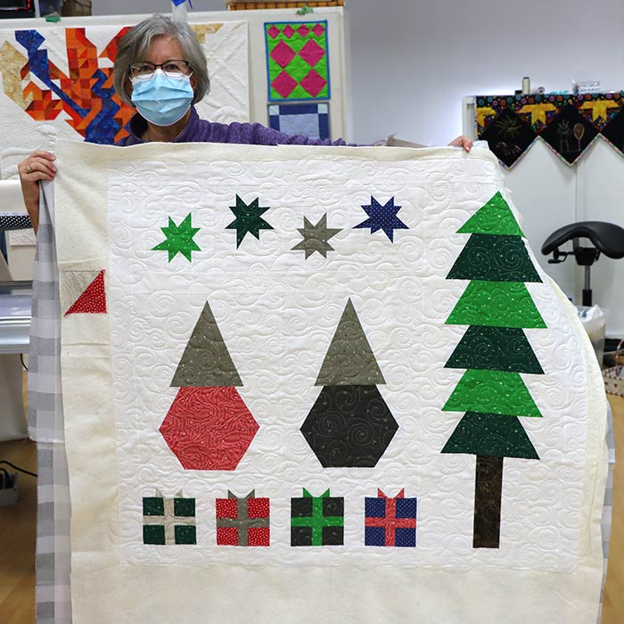 image of a woman holding up a Christmas quilt at Quilted Joy
