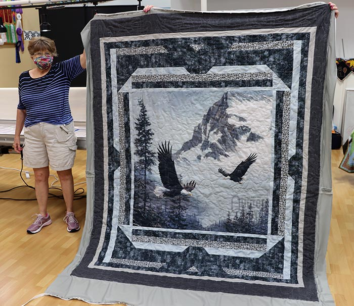 Mary Jane shows off her Eagle quilt after quilting it on a longarm machine at Quilted Joy