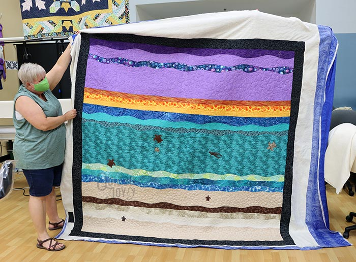 Michelle shows off her original beach quilt after quilting it at Quilted Joy