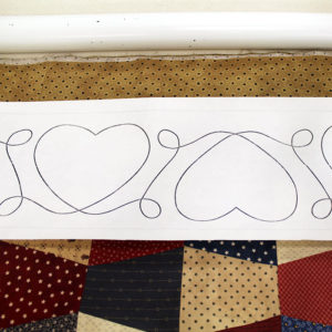 Portion of a Hearts Border Paper Pantograph spread across a quilt