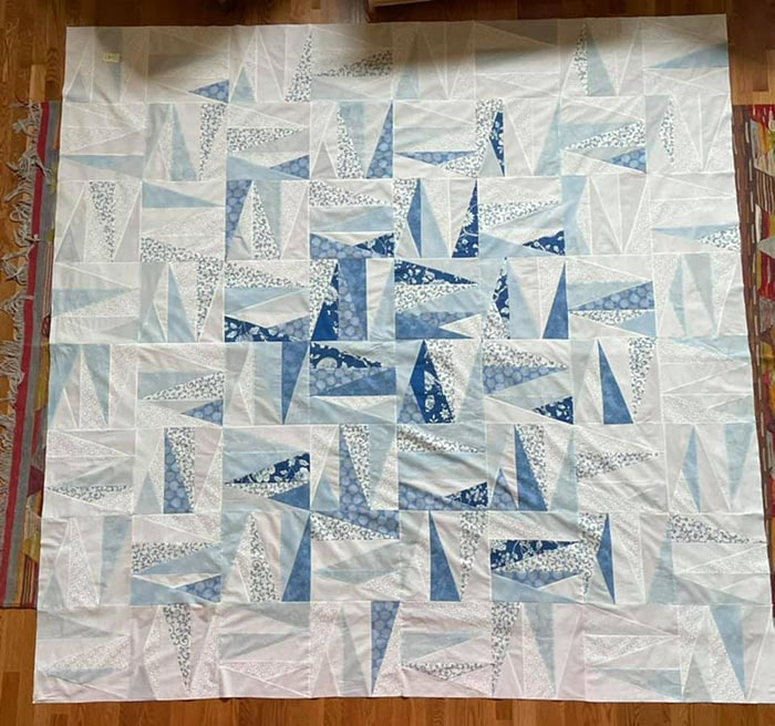 Overhead view of an unquilted quilt top with blue and white fabrics