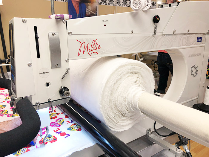 Large quilt sandwich rolled around a APQS Millie take up bar