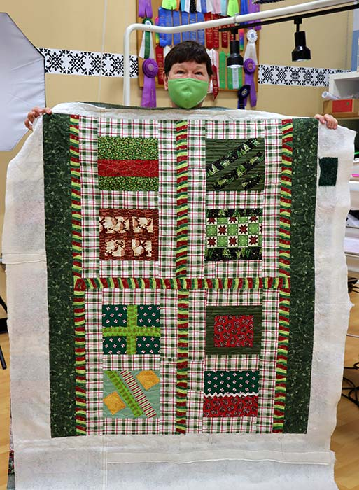 image of a woman holding up her Christmas quilt after quilting it on a longarm at Quilted Joy