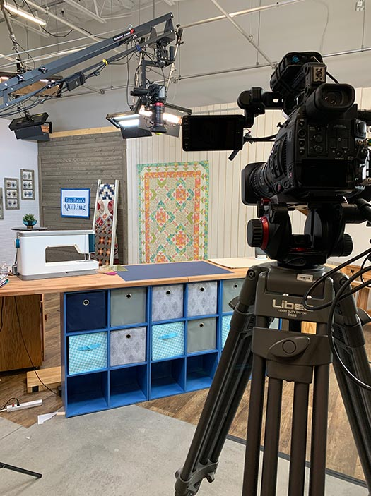image of the Fons & Porter Love of Quilting TV show set with the Summer Saturday quilt hanging in the background