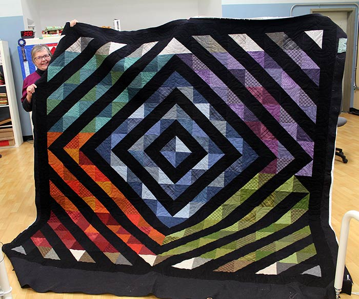 image of woman holding up a large quilt with a radiating diamond design