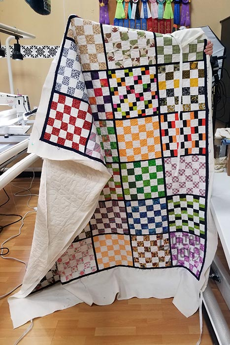 image of someone holding up a quilt with lots of small patchwork pieces